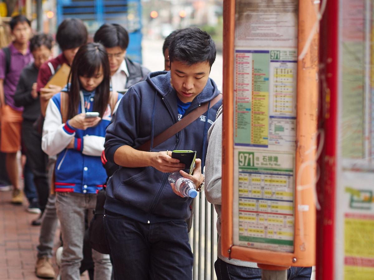 Folk er folk - også mens de venter på bussen i Hong Kong.